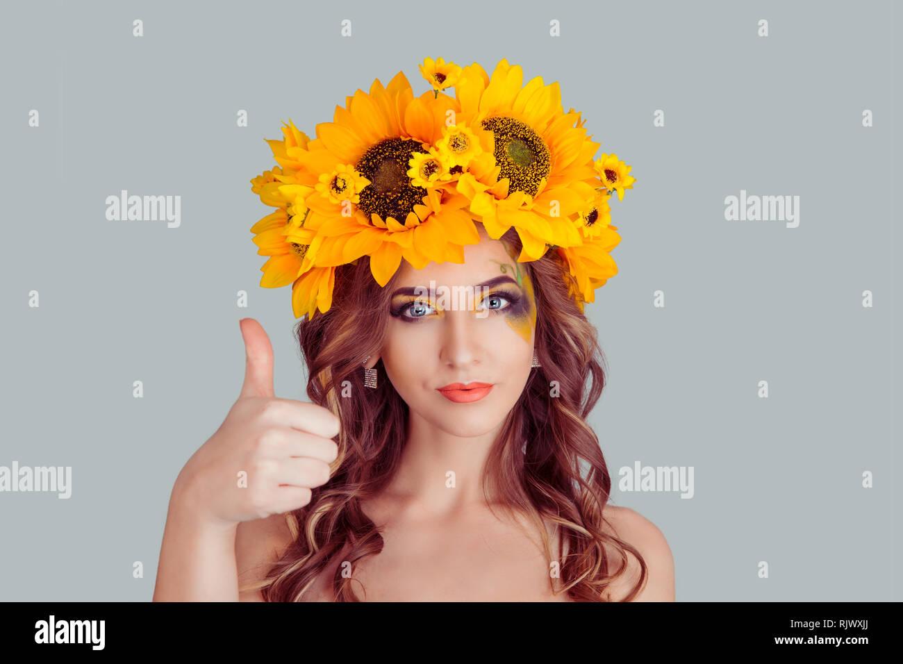 Felice giovane donna con fascia floreale che mostra i pollici come segno di mano. Ragazza con corona da girasoli sulla testa isolata su uno sfondo grigio con cop Foto Stock