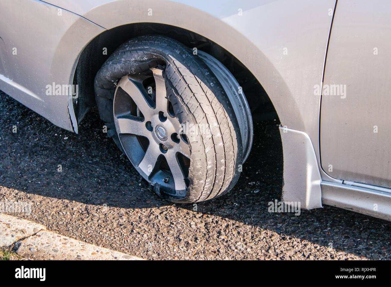 Pneumatico di una macchina che ha una espulsione con rim e danneggiamento auto. Il pneumatico è venuta fuori del cerchio. Pneumatico è su una vettura che è su una strada asfaltata Immagini Stock