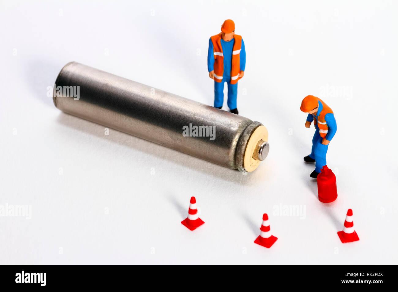 Diorama concettuale immagine di gestione dei rifiuti costituiti da miniture figura operai guardando una batteria Immagini Stock