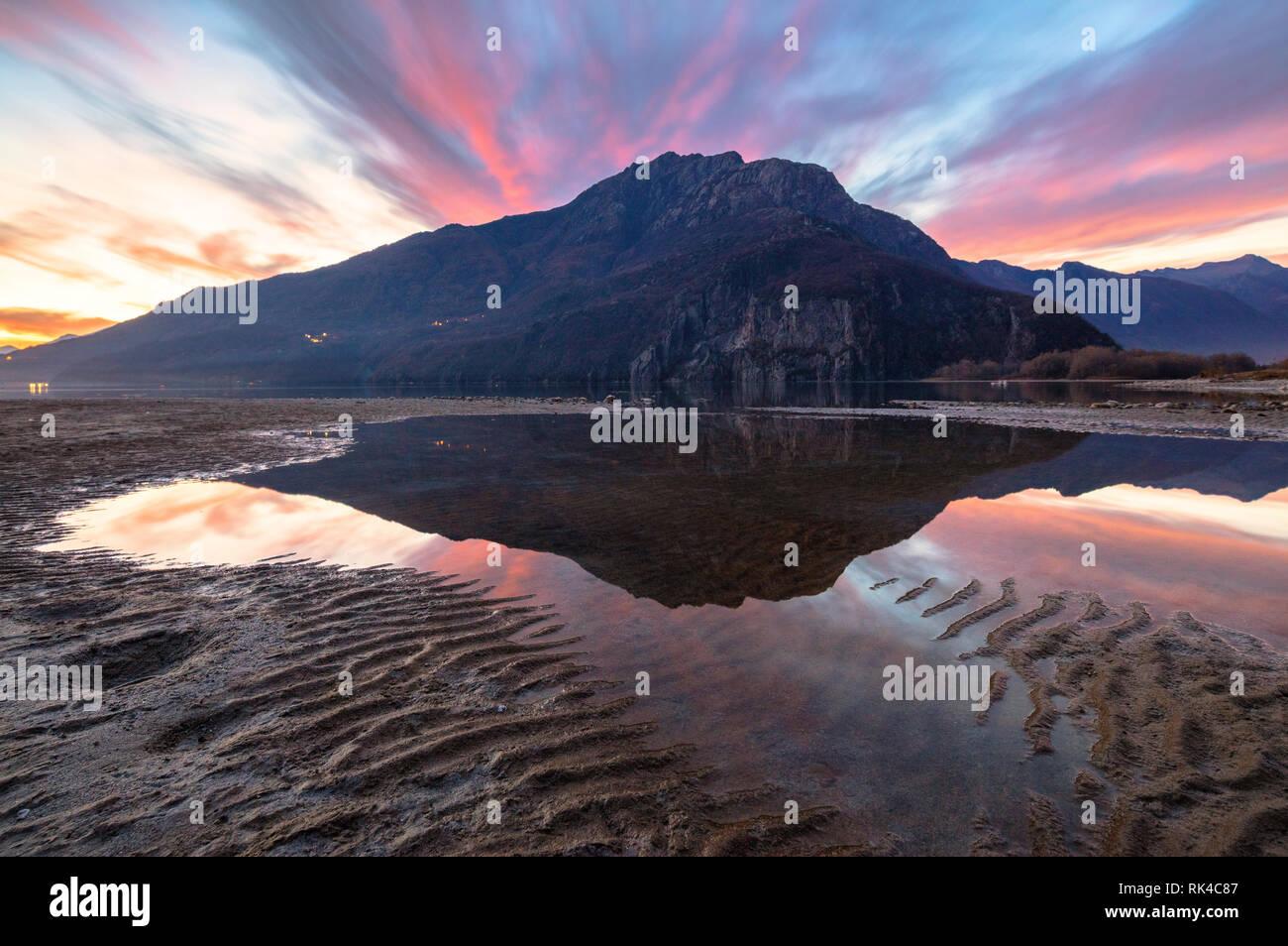 Monte Berlinghera specchiata in acqua al tramonto, Novate Mezzola, Val Chiavenna, provincia di Sondrio e della Valtellina, Lombardia, Italia Foto Stock