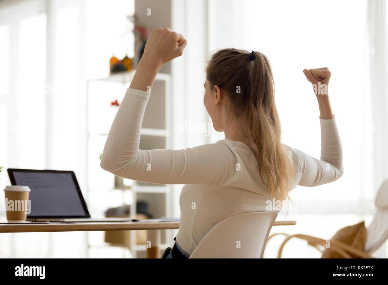 Vista posteriore a Excited donna lettura buona notizia in un messaggio di posta elettronica Immagini Stock