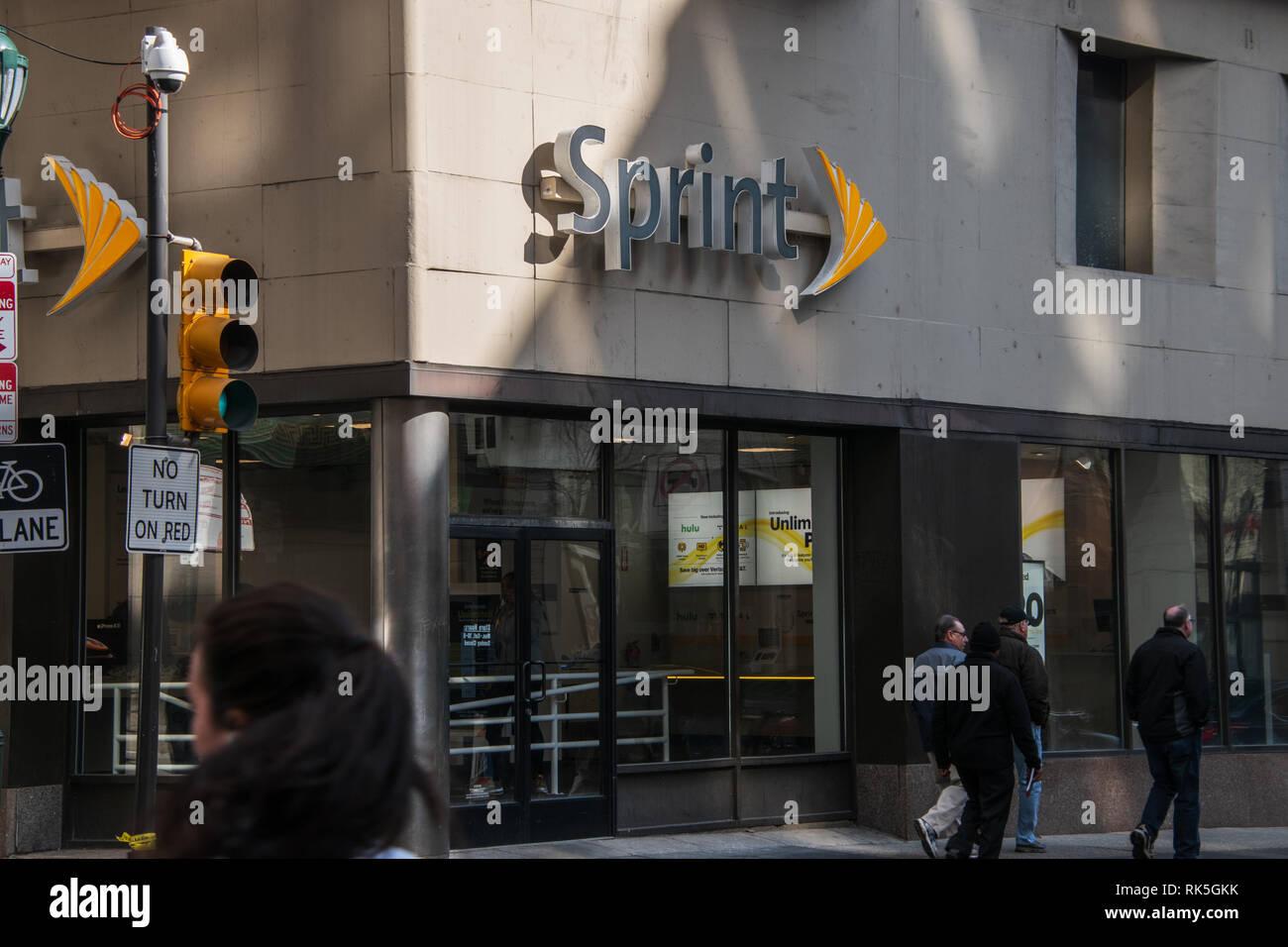 Philadelphia, Pennsylvania - Febbraio 5, 2019: Store anteriore di un negozio Sprint che mostra il logo Sprint e gente che cammina sulla strada di fronte al Immagini Stock
