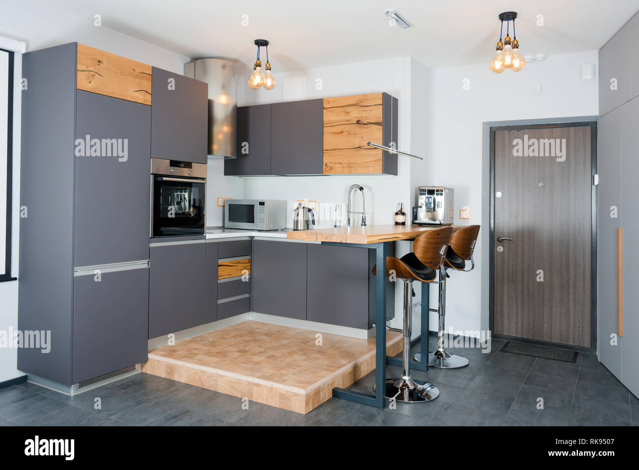 Cucina moderna con interni con luci accese. Brown tavolo in legno e ...