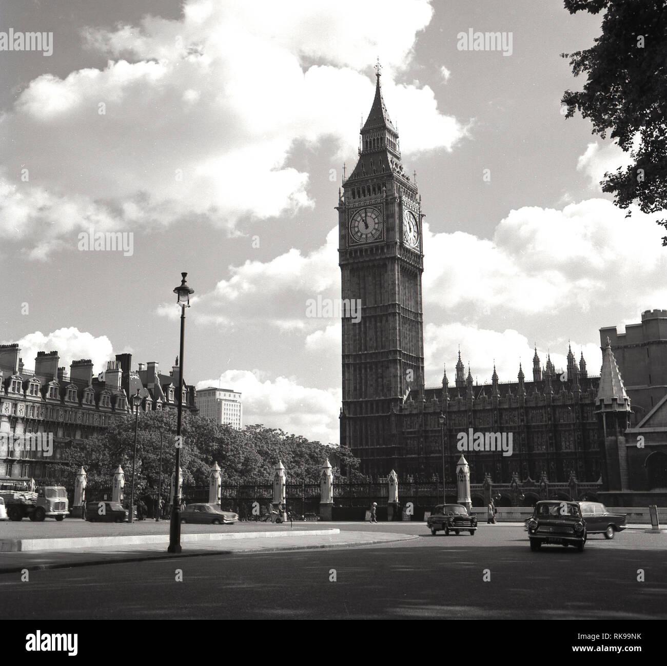 Anni sessanta, storico, autovetture andando attorno a Piazza del Parlamento accanto al Elizabeth o Torre dell Orologio Come si è precedentemente noto, all'estremità settentrionale del Palazzo di Westminster, la casa del governo del Regno Unito. Stabilite da Sir John Barry in 1868, Piazza del Parlamento divenne Bretagna la prima rotatoria nel 1926. La torre, a cui si fa riferimento anche come 'Big Ben', è stato progettato da Augusto Pugin, un architetto inglese noto per il suo lavoro nel revival gotico stile di architettura e quando completato nel 1859 è stato il più grande orologio rintocchi nel mondo. Immagini Stock