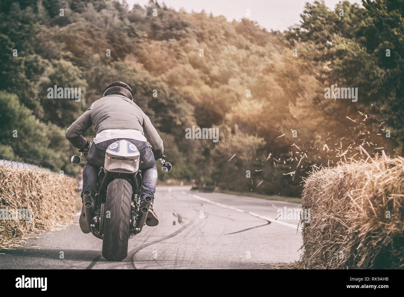 Motociclista accelerando il suo moto su una dritta strada forestale con pezzi di fieno soffiatura di una balla di fieno Immagini Stock