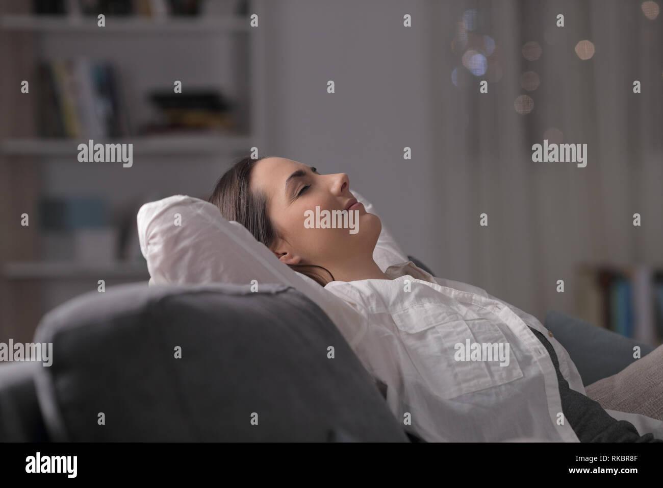 Vista laterale ritratto di una donna appoggiato comodamente seduto su un divano nella notte a casa Foto Stock
