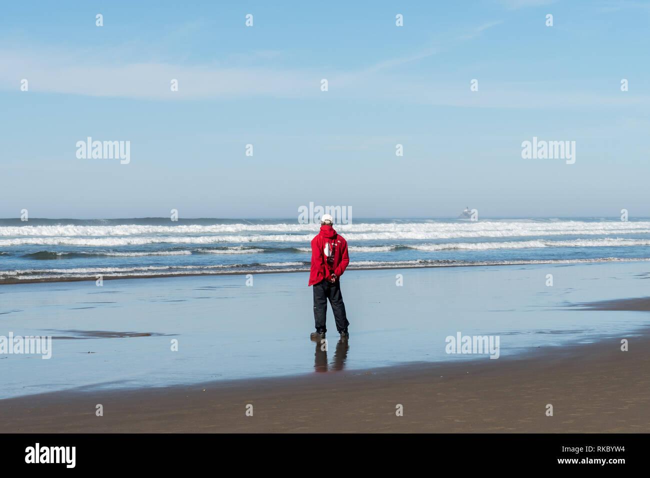 Un membro di Haystack Rock programmi di sensibilizzazione con la sua firma di felpa rossa orologi e osserva l'oceano Immagini Stock