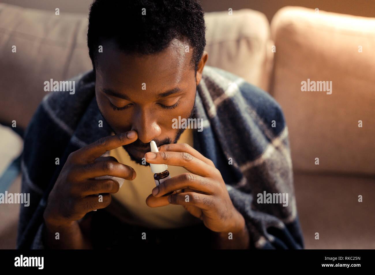 Afro-americano di uomo con spray nasale pur avendo acceso naso Foto Stock