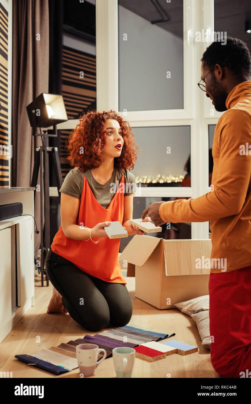 Il marito aiutando la moglie nella scelta di colore per mobili Immagini Stock