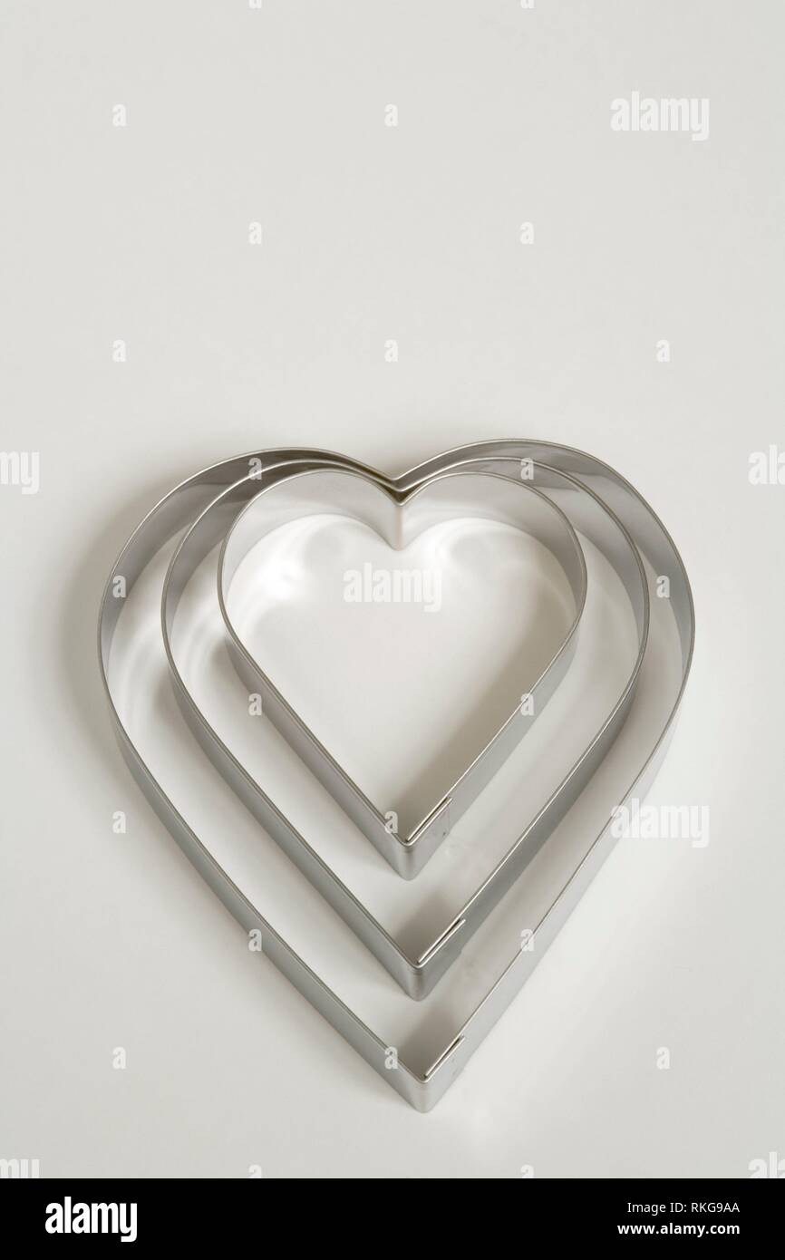 Un set di tre a forma di cuore ad cookie cutters su uno sfondo bianco. Foto Stock