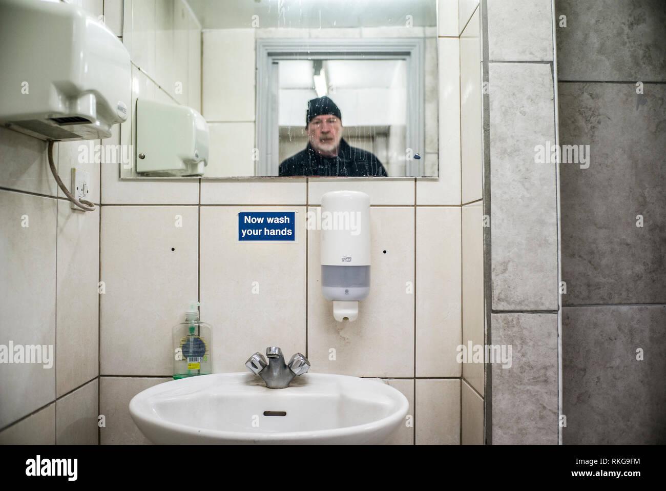 Uomo Barbuto in specchio, lavarsi subito le mani segno, wc pubblico,dell'essiccatore della mano, dosatore per sapone liquido, Immagini Stock