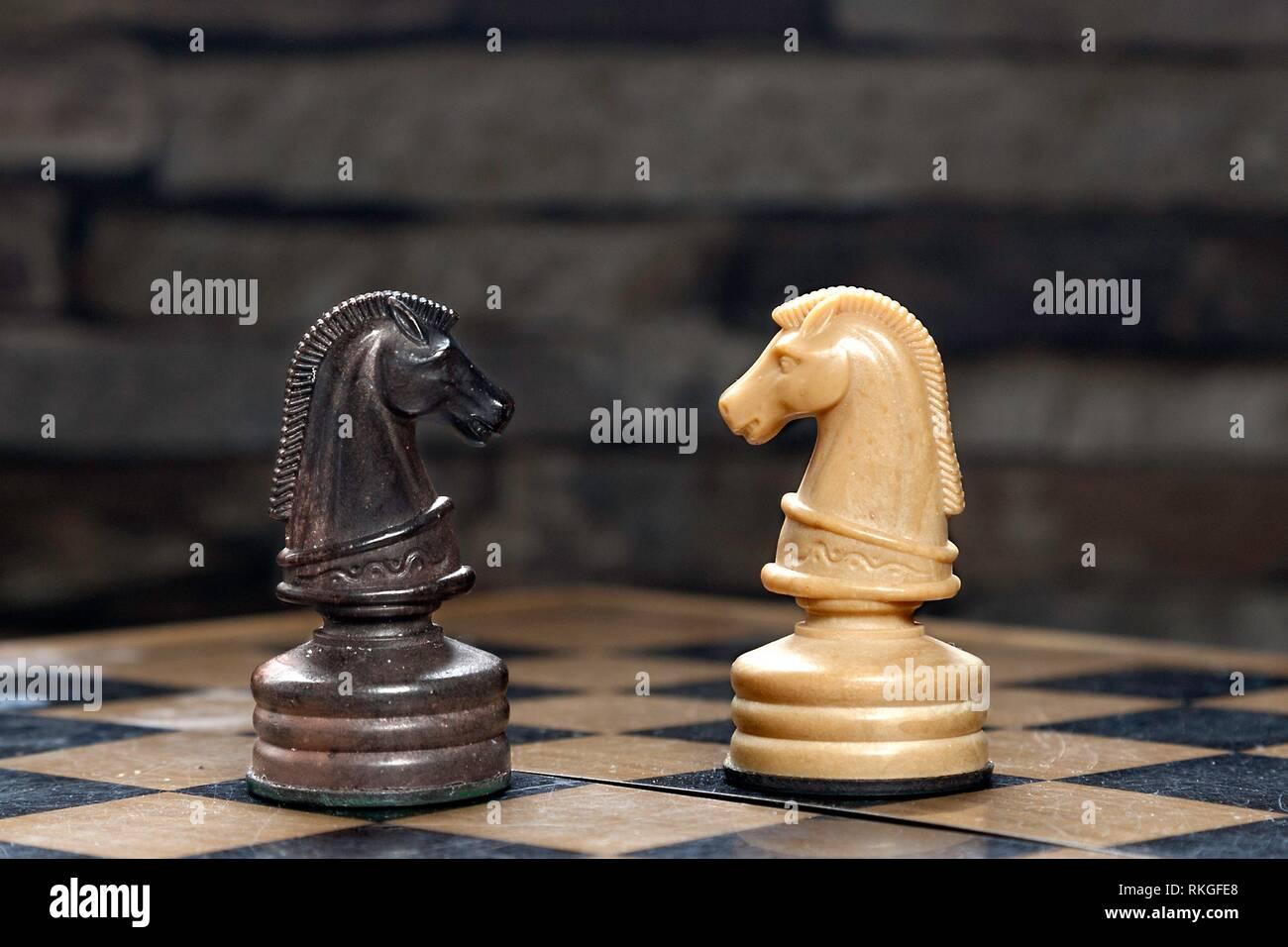 I cavalli di scacchi di fronte a scacchiera con la pietra. Immagini Stock