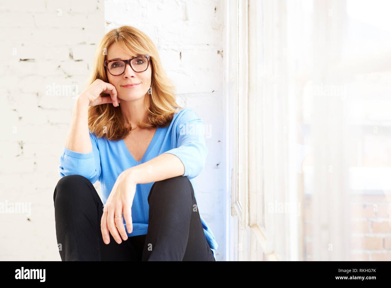 Ritratto di sorridere donna di mezza età rilassante mentre è seduto alla  finestra e guardando a 97a10d1384ba