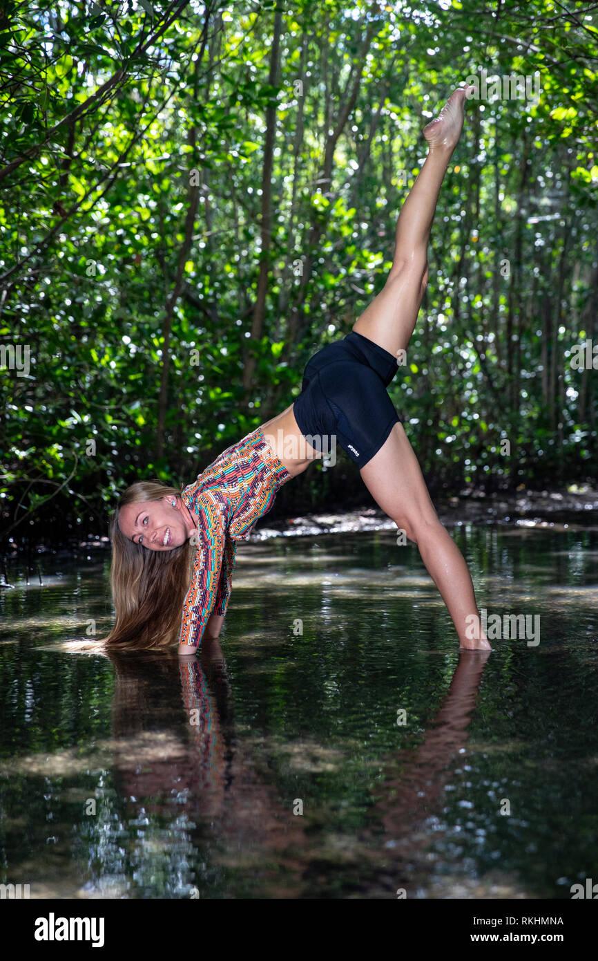 Giovane donna a praticare yoga (Cane con la testa in giù Split (Cane su tre zampe) in un ambiente naturale - Fort Lauderdale, Florida, Stati Uniti d'America Immagini Stock