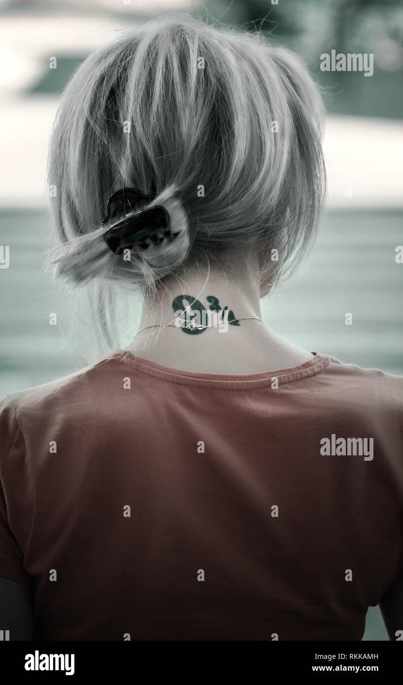 Donna con la cenere i capelli colorati e nuca tatuati in piedi in strada. Immagini Stock