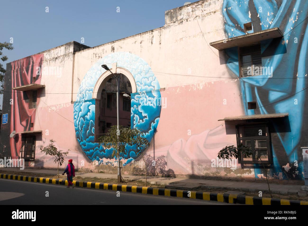 Donna cammina davanti a un grande murale dipinto sul lato dell'edificio in Colonia Lodhi, New Delhi, India Immagini Stock