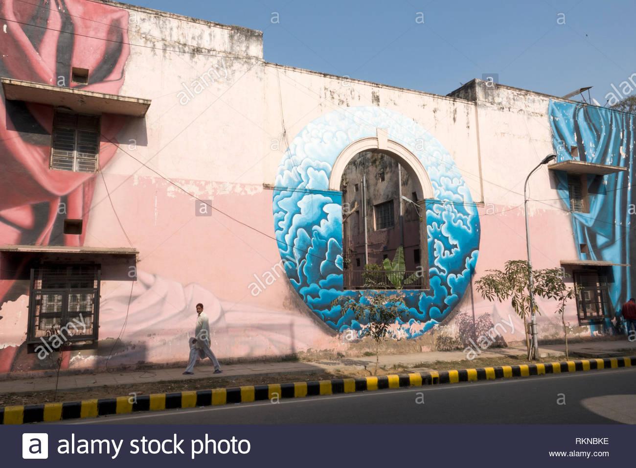 L'uomo cammina davanti a un grande murale dipinto sul lato dell'edificio in Colonia Lodhi, New Delhi, India Immagini Stock