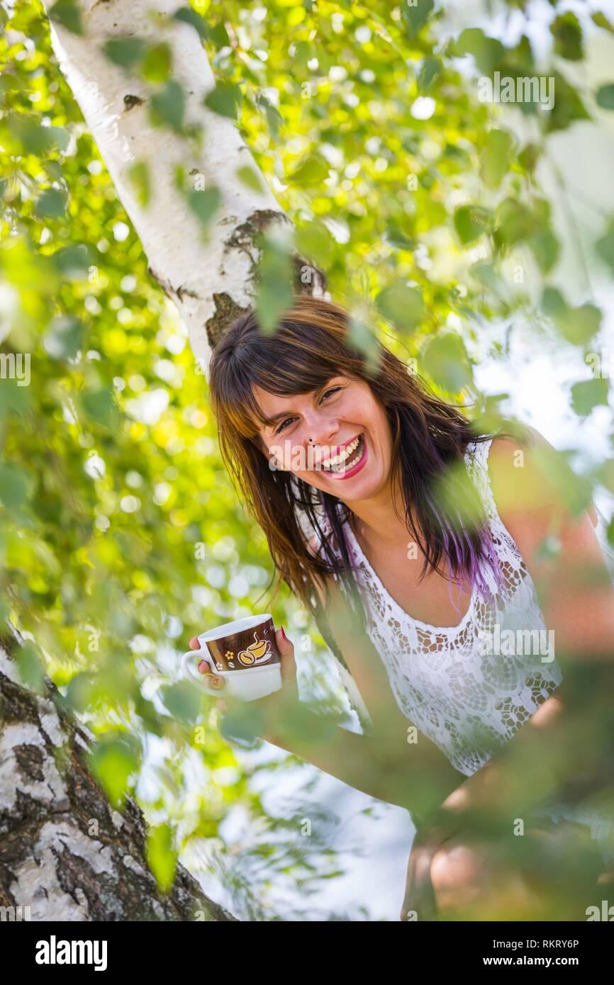Attraente ragazza adolescente è di bere il caffè in natura guardando la telecamera extreme ridere felice e sorridente risatina sogghignando espressione espressiva Immagini Stock