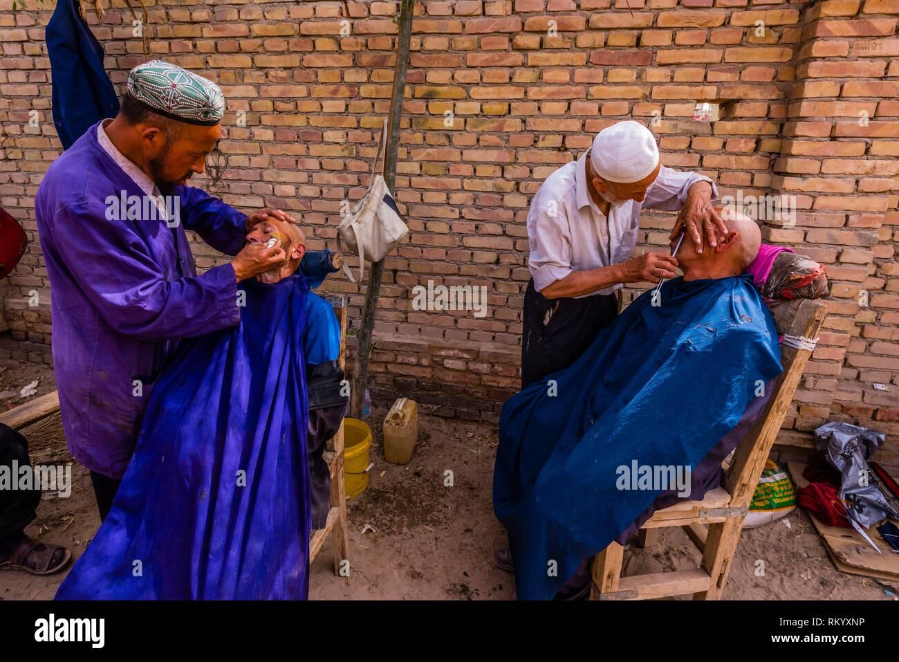 Uyghur uomini di ottenere un taglio di capelli e la barba al mercato settimanale a Opal (Upal), un villaggio lungo l Autostrada Karokoram (50 km. a sud-ovest di Kashgar) che Immagini Stock