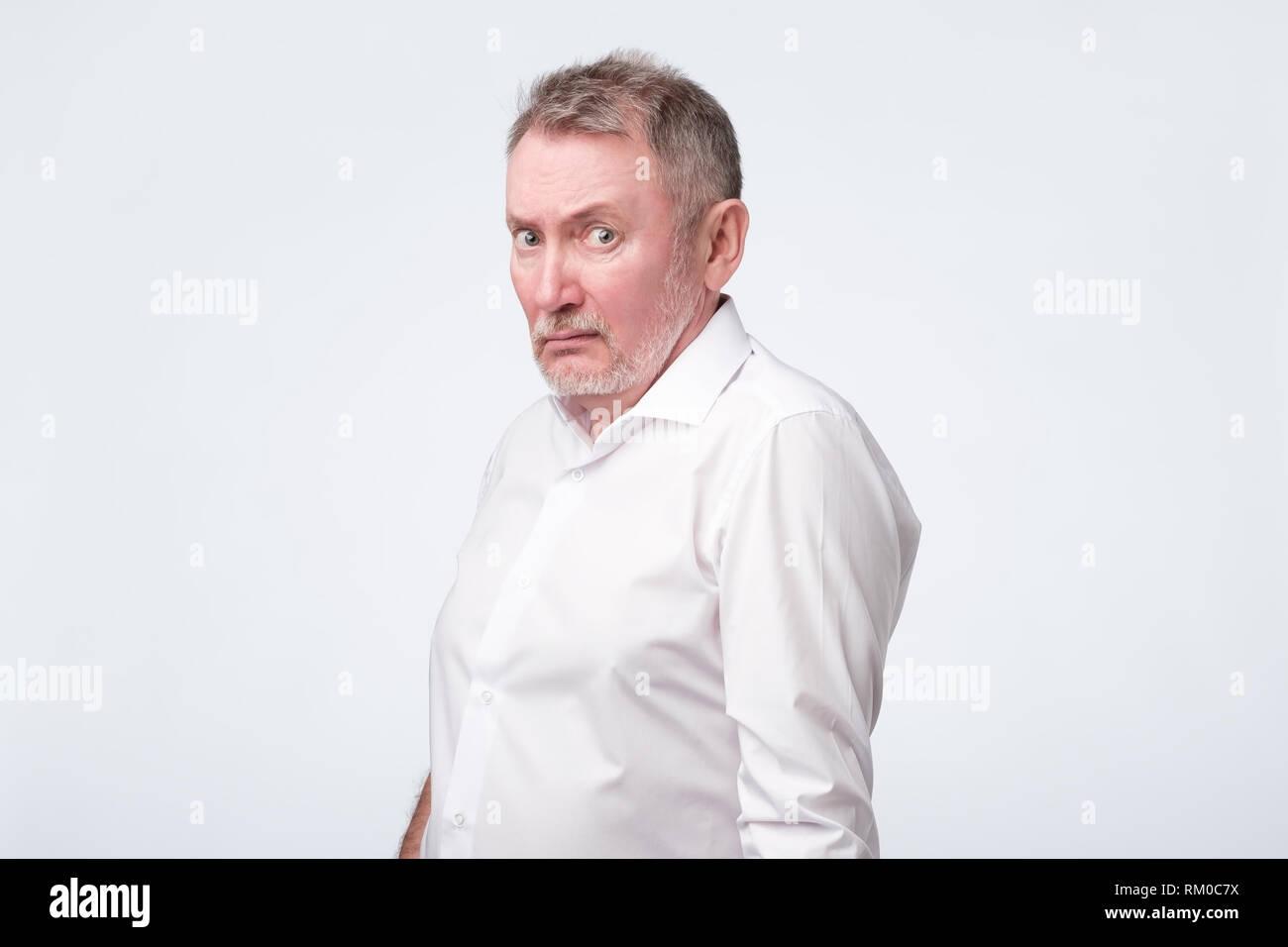 Senior Uomo in camicia rossa accigliata e strizzare gli occhi, mostrando incredulità o dubbio Immagini Stock