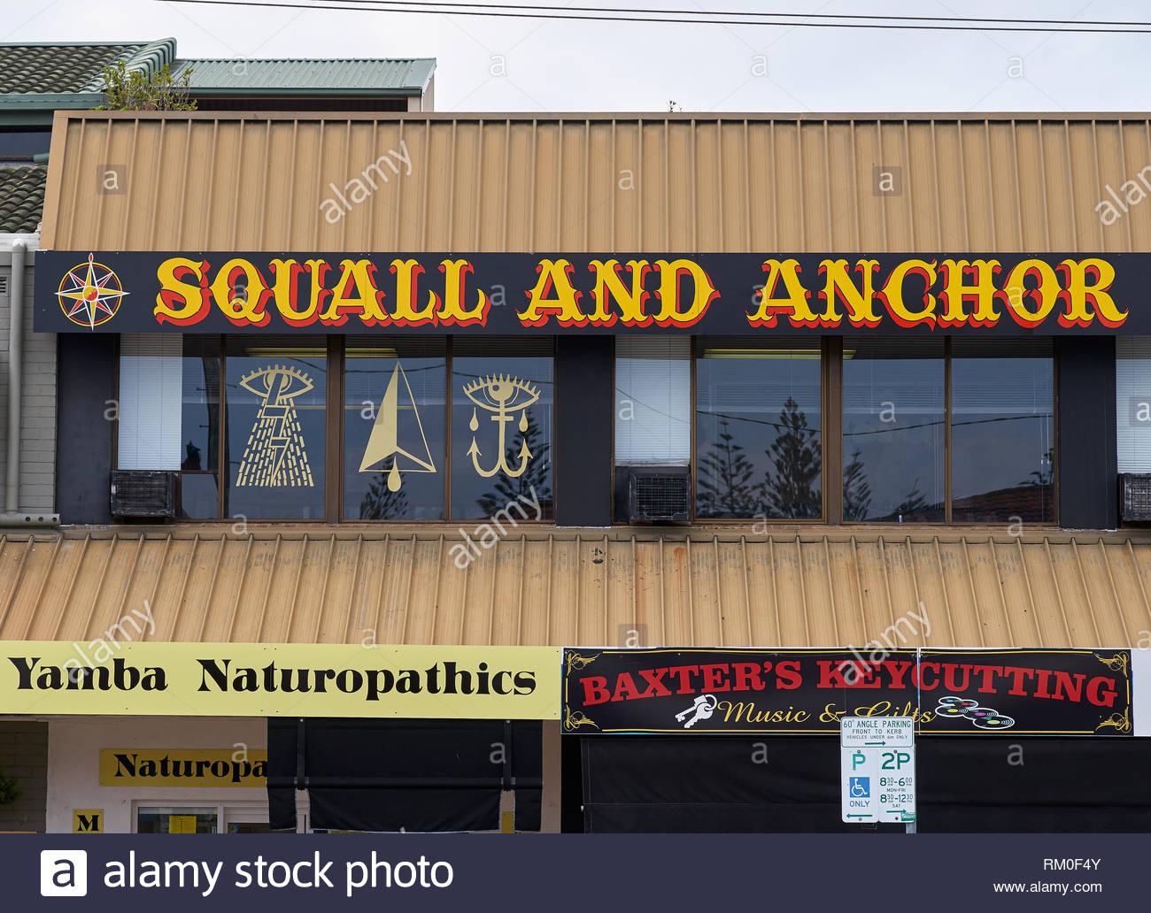 Shop di smistamento del traffico nella strada principale di Yamba - 'Squall ed ancoraggio tatuaggio', 'Yamba Naturopathics' e 'Baxter's Keycutting' - con la simbologia satanica. Immagini Stock