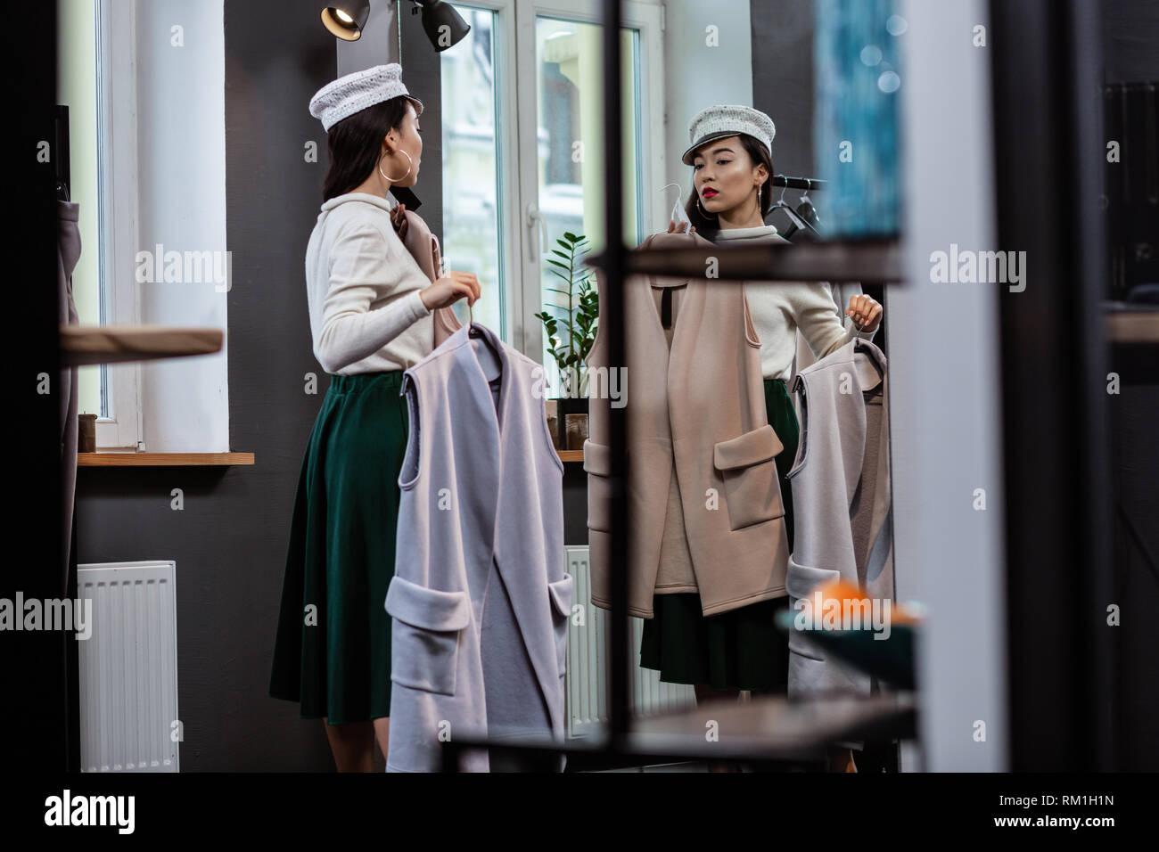 Oung dai capelli scuri piuttosto asiatici donna nel quartiere alla moda di copricapi in piedi di fronte allo specchio Immagini Stock