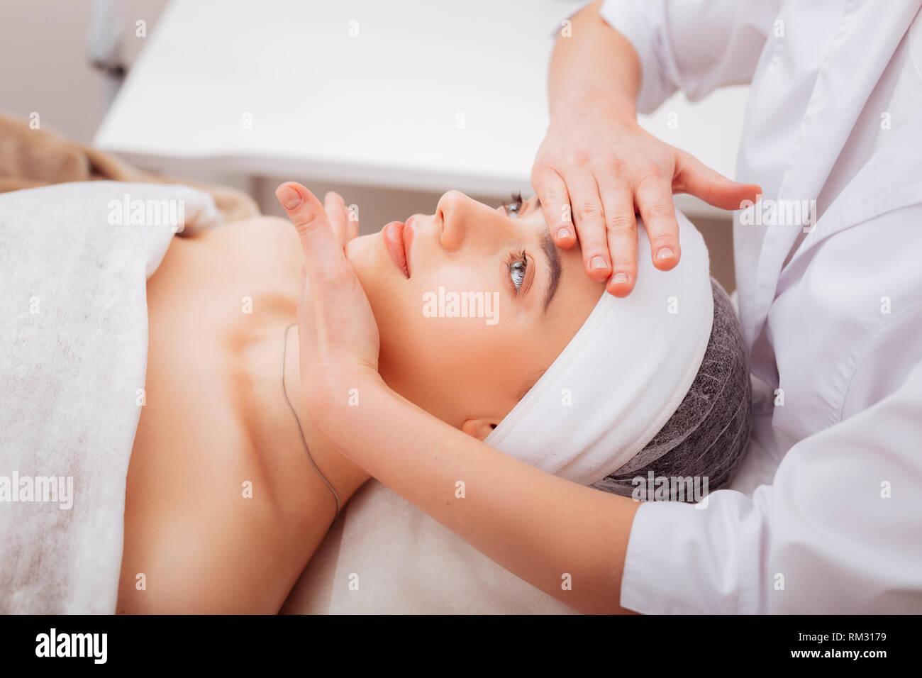 Bella giovane donna godendo del suo massaggio del viso Immagini Stock