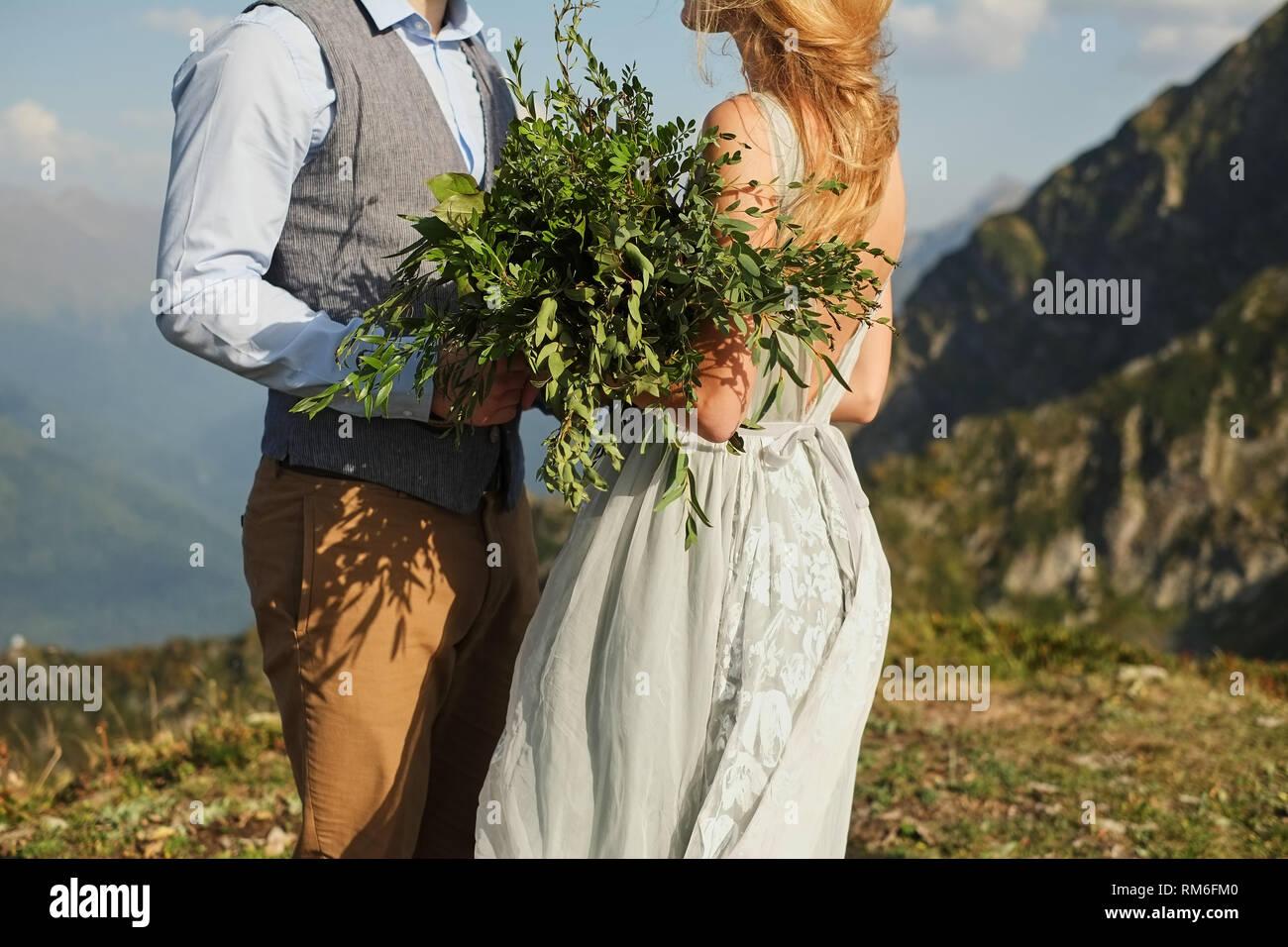 La sposa chiuse gli occhi e sussurra qualcosa al suo fidanzato, close-up, bouquet verde sullo sfondo di montagne Immagini Stock