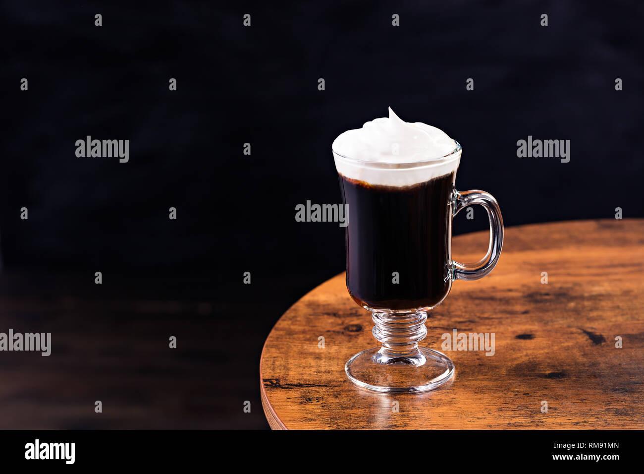 Caloroso Whiskey Irish Coffee Cocktail su un tavolo Foto Stock