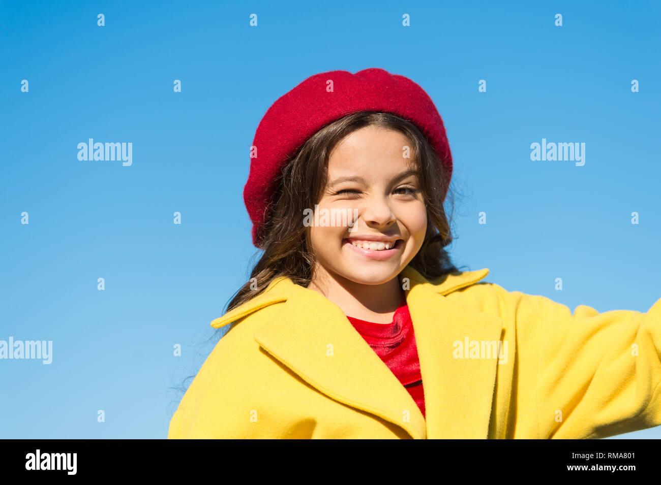 Cose che andrà bene. Wink ragazza faccia allegra cielo blu sullo sfondo. Kid ragazza indossare cappello e il cappotto allegro soddisfatti di tutto. Buon umore emozioni positive. Giocoso bambino allegro espressione. Immagini Stock