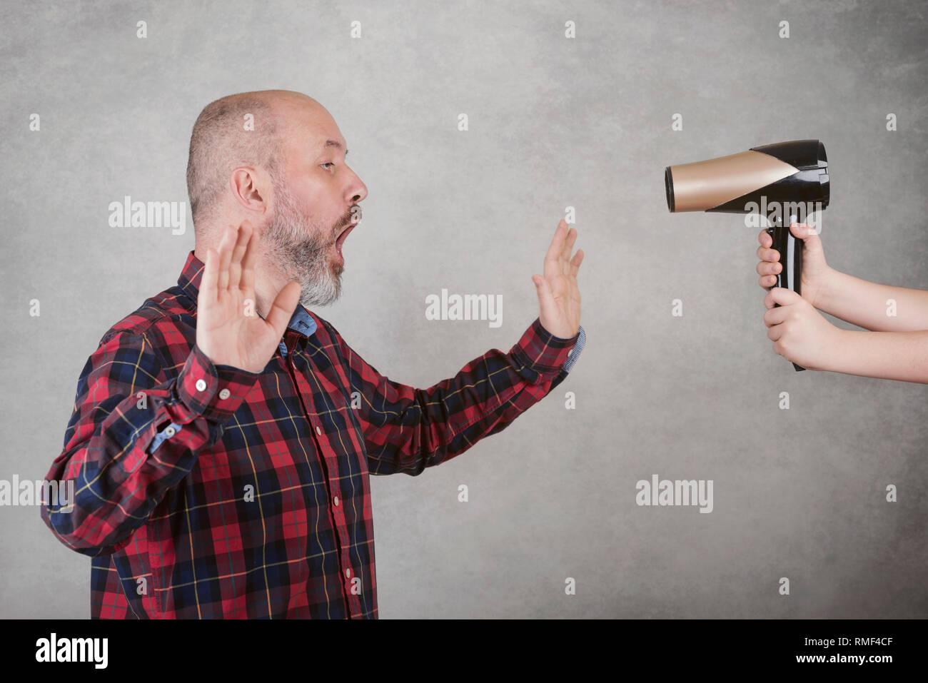 Sorpreso adulto uomo calvo accanto a un asciugacapelli contro uno sfondo grigio Immagini Stock