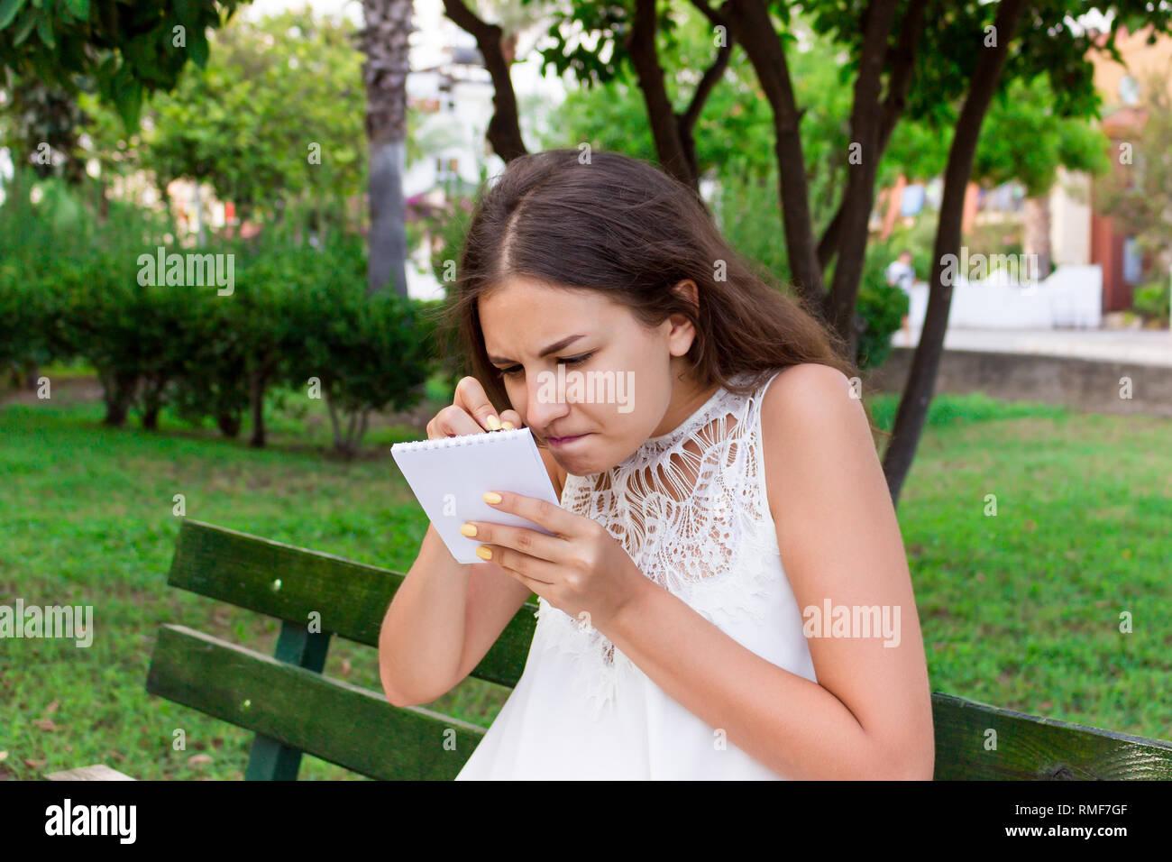 La donna sta scrivendo la sua entusiasmanti idee nel suo blocco note con grande concentrazione. Immagini Stock