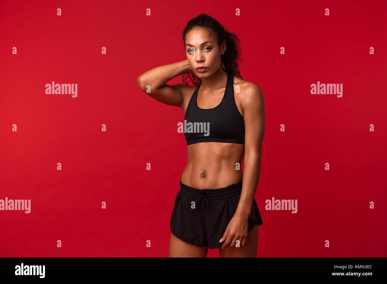 Ritratto di Ben costruita americano africano donna in nero permanente sportswear isolate su sfondo rosso Immagini Stock