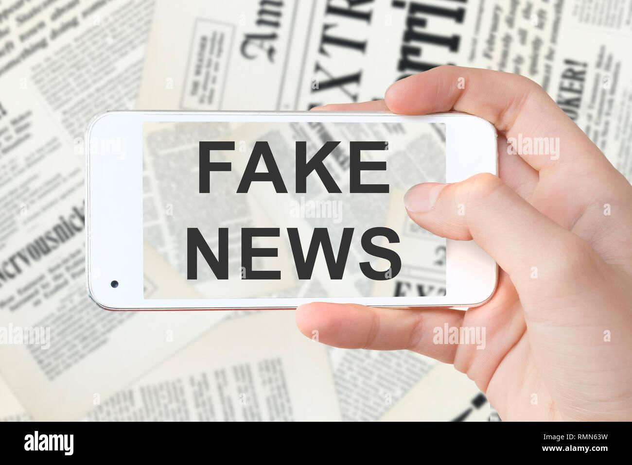 Falsa notizia scritta su un computer lo schermo dello smartphone, offuscata quotidiani sullo sfondo Immagini Stock