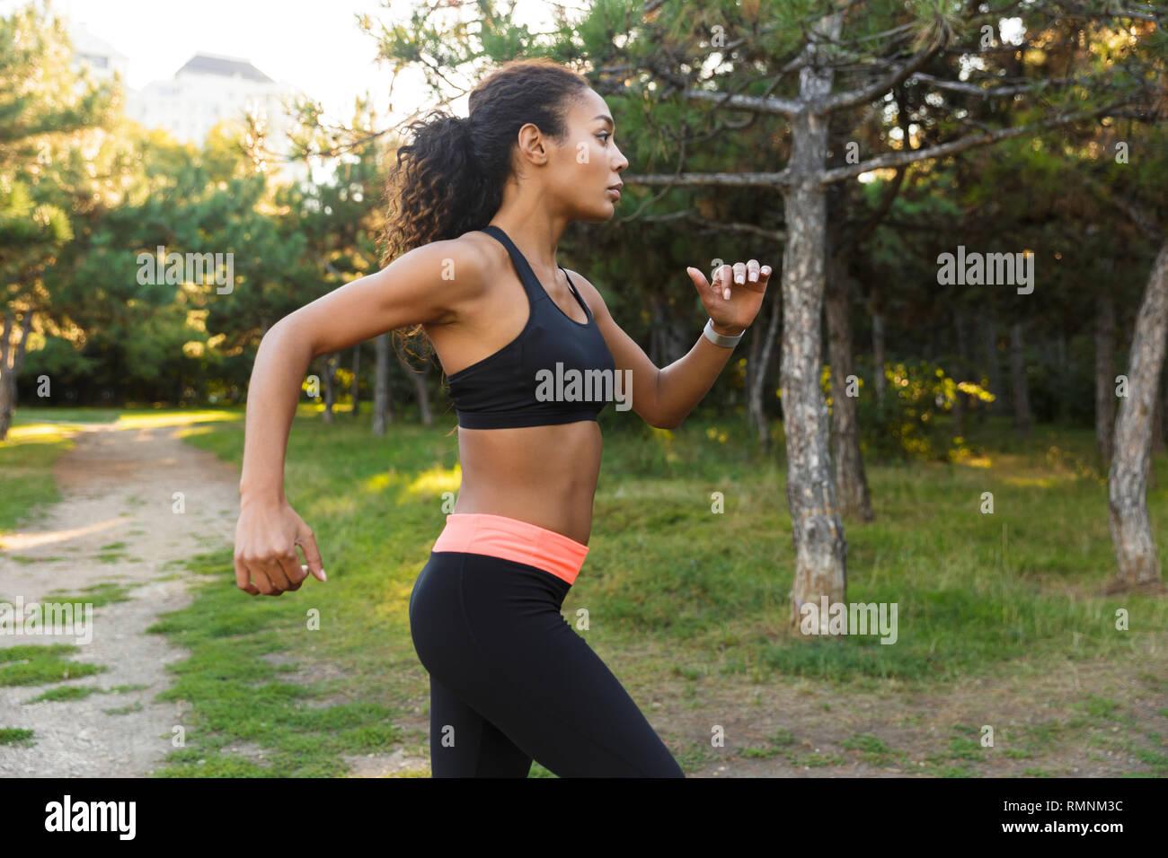 Ben costruita americano africano donna 20s indossare tuta nera in esecuzione attraverso il parco verde Immagini Stock