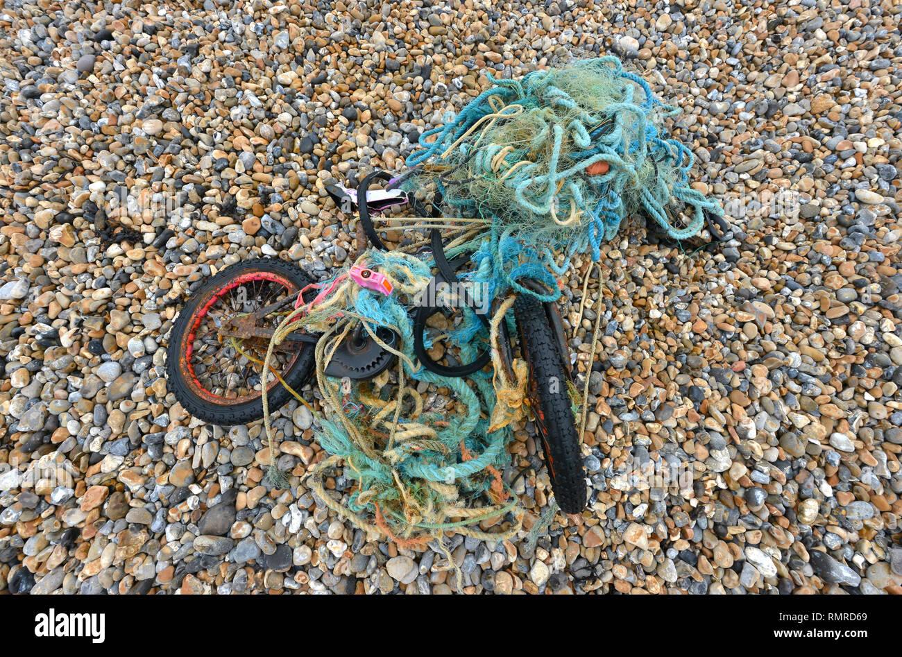 Vecchia moto aggrovigliato in una plastica rete da pesca, scartati su una spiaggia, East Sussex, Regno Unito Immagini Stock