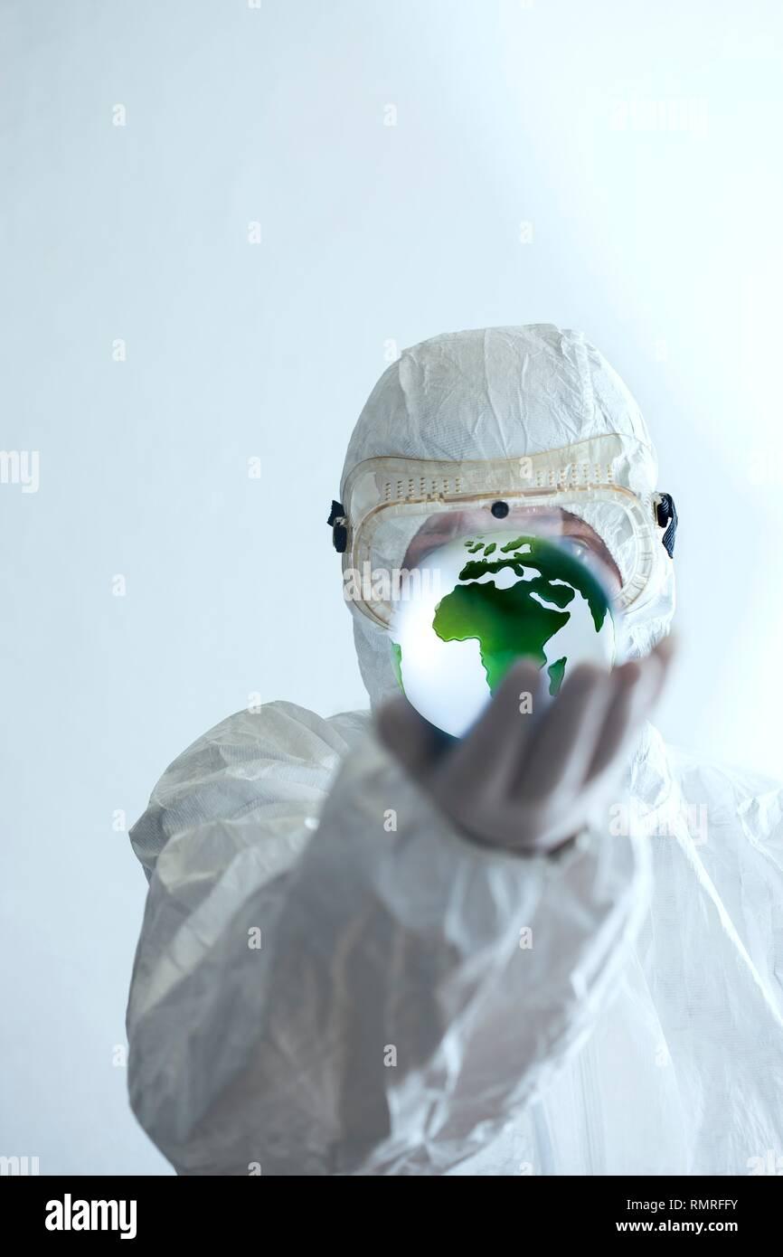 Scienziato in abbigliamento protettivo azienda globo nella sua mano. Immagini Stock
