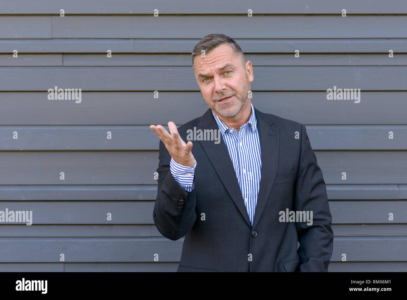 Imprenditore persuasiva gesticolando con la sua mano come egli fa un punto o spiega con un look di empatia contro un muro grigio con spazio di copia Immagini Stock
