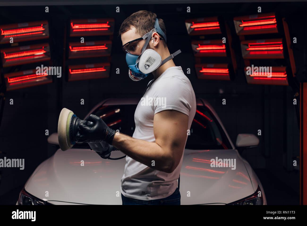 Giovane uomo la preparazione per la lucidatura di auto in servizio. close up vista laterale foto. Tempo libero, hobby Immagini Stock