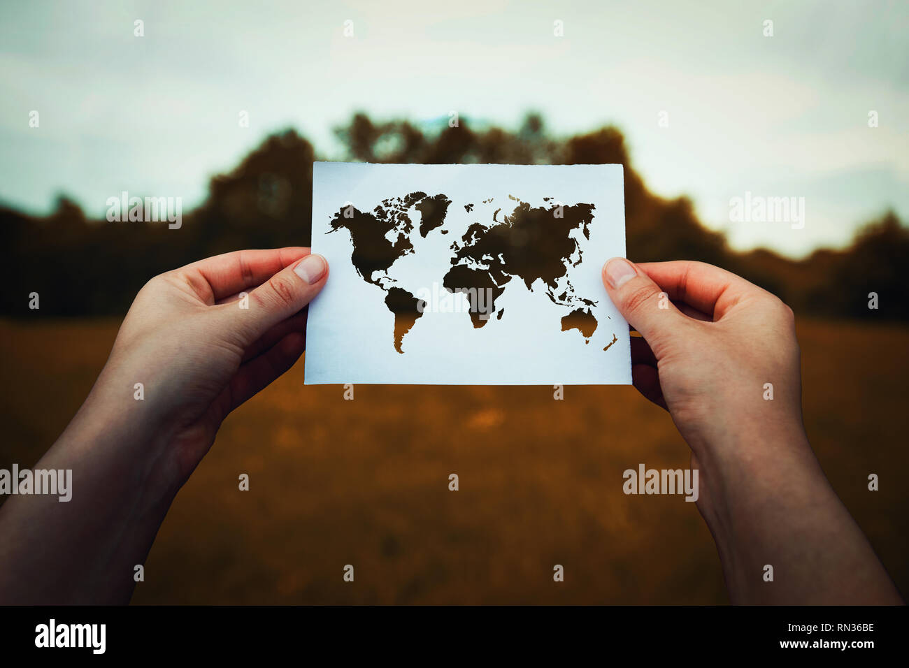 Il cambiamento climatico il problema, distruzione del concetto di natura. Le mani umane tenendo un foglio di carta con la mappa del mondo icona sopra un erba secca dello sfondo dei campi. Global Immagini Stock
