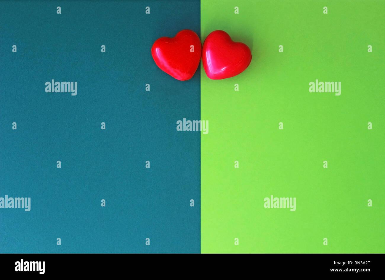 Amore, due cuori rossi affiancati su sfondo verde Immagini Stock