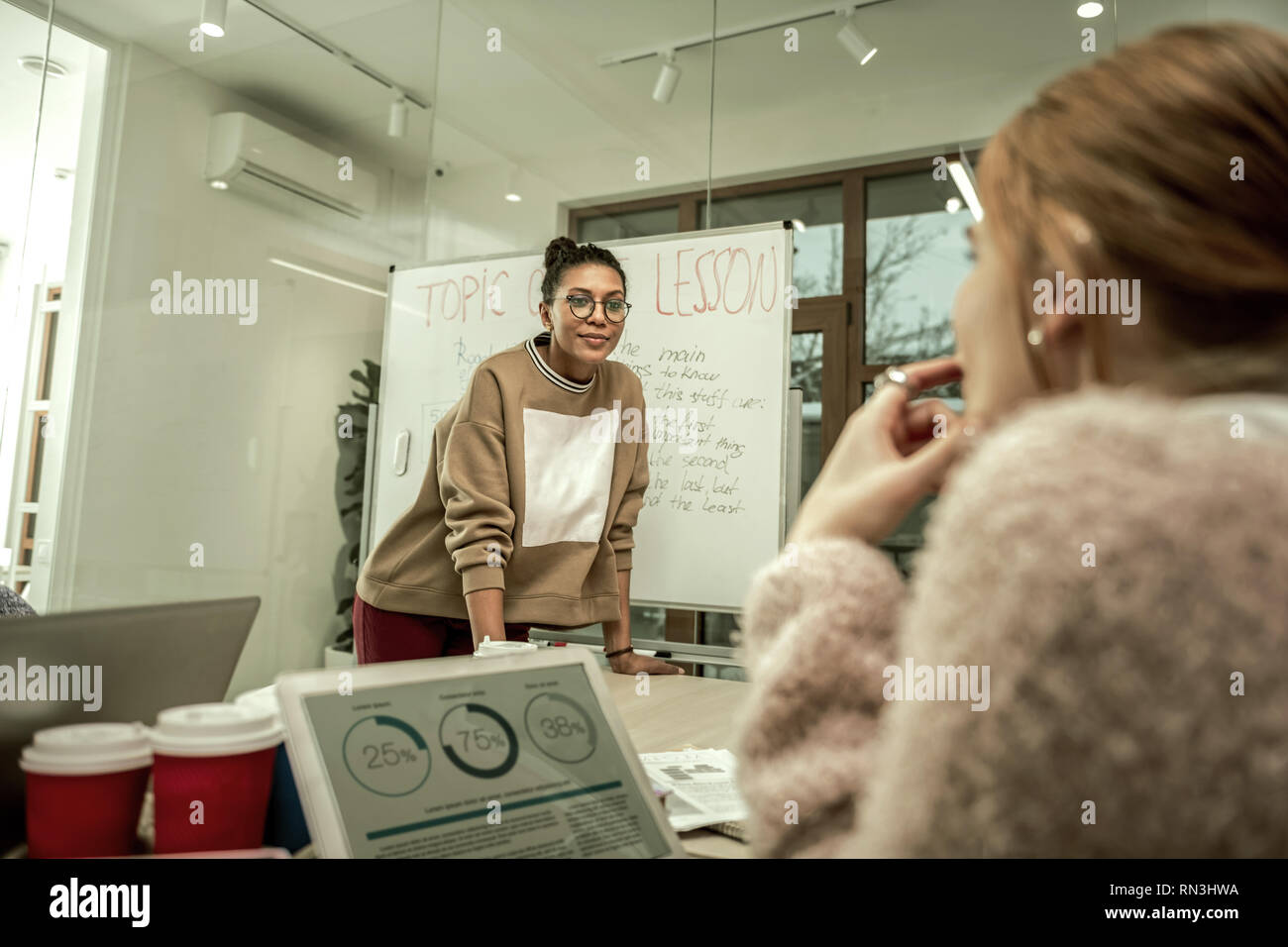 Giovane studente indossa felpa elegante ascoltando studente Immagini Stock