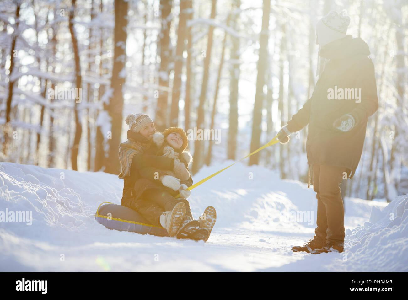 La famiglia felice godendo Sleigh Ride Foto Stock