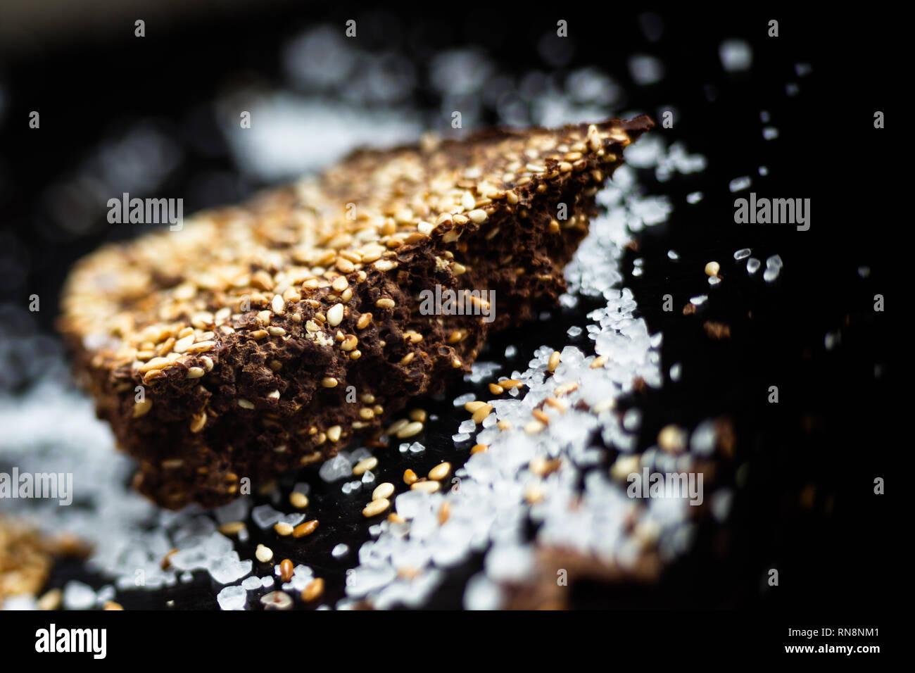 Il lusso artigianale di cioccolato fondente con seasame e sale marino, sfondo nero Immagini Stock