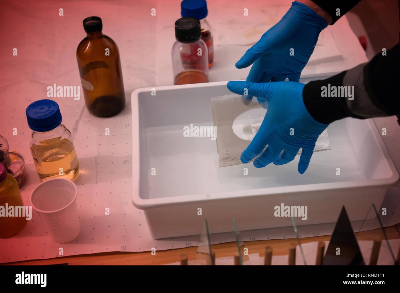 Fotografo bagna un ambrotype in una soluzione chimica. Piastra umida collodio processo. Le attrezzature della camera oscura. Immagini Stock