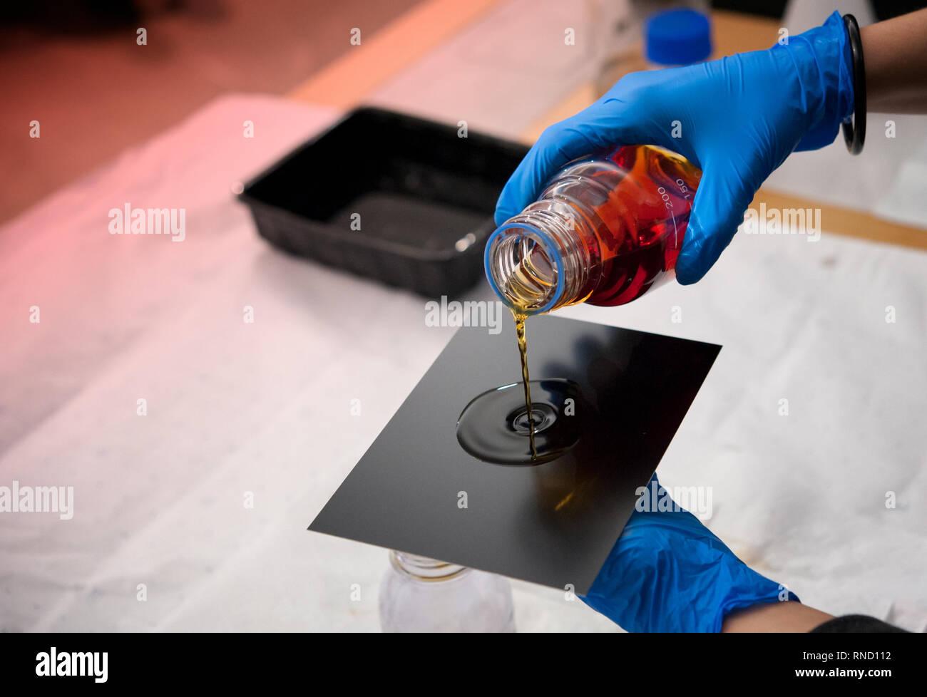 Fotografo riversa collodio soluzione sul nero sottile piastra di ferro. Piastra umida collodio processo. Immagini Stock
