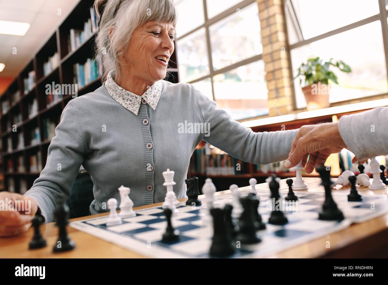 Senior donna giocando una partita a scacchi con il suo partner. Allegra donna anziana rilassarsi giocando a scacchi. Foto Stock