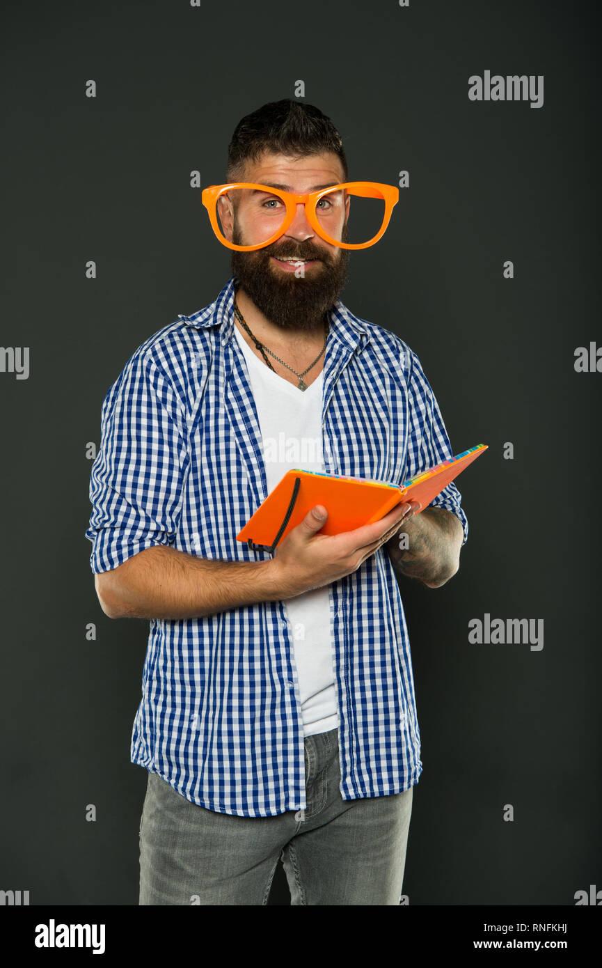 Corsi di istruzione per adulti. Auto educazione nozione. Club letterario. Libro di lettura come hobby. Studio è divertente. Tanga uomo barbuto funny occhiali tenere il blocco note o un libro. La lettura di questo libro. Fumetti e umorismo senso. Immagini Stock