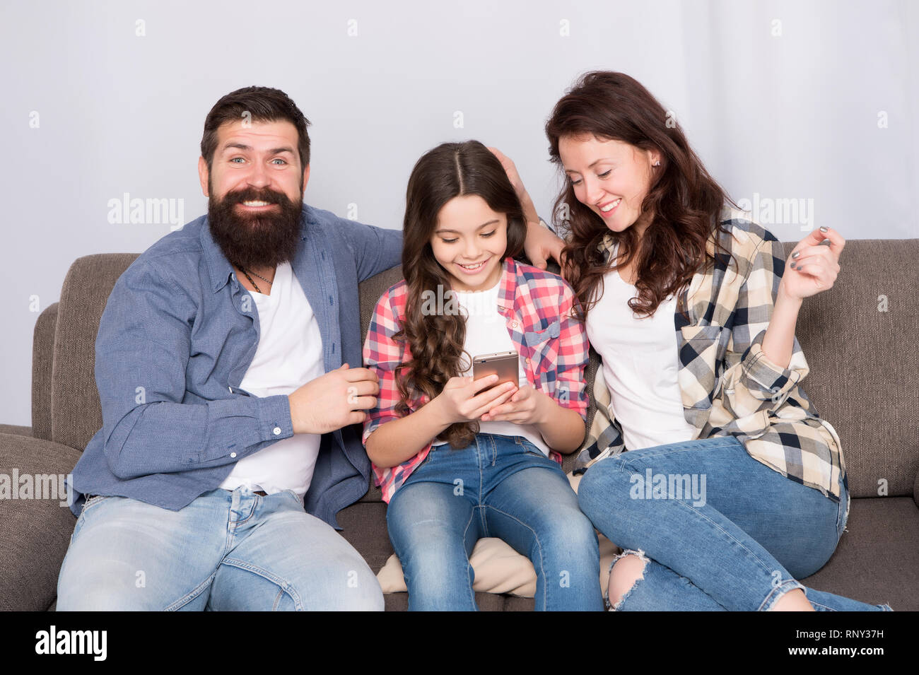 Il controllo genitori. Famiglia trascorrere weekend insieme. Bambino bambina utilizza lo smartphone con i genitori. Famiglia amichevole divertirsi insieme. Mamma e papà occupato figlia rilassante sul lettino. Vacanza in famiglia. Immagini Stock