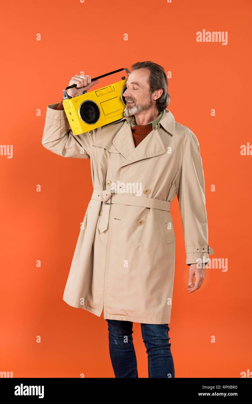 Moda uomo senior azienda boombox giallo isolato su Orange Immagini Stock 64273358c015